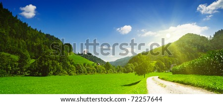 Idyllic countryside panoramic view. Green meadow, hills, field and road under blue sky in sun rays. Slovenia.