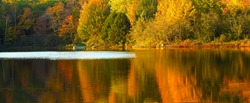 Idyllic fall foliage scene with reflections on lake with a wisp of wind ripples.
