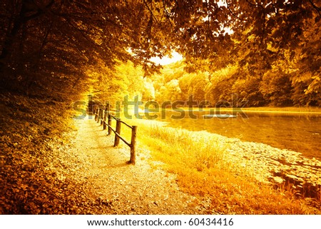 Idyllic forest path by the lake in autumn - stock photo