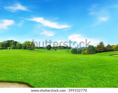 Idyllic golf course with forest and sand trap. Summer landscape, park.