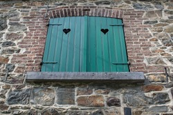Idyllic heart-shaped, wooden, green window shutters in a rustic stone cottage in the French speaking part of Belgium.
