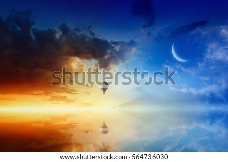 Idyllic heavenly background - colorful hot air balloon flies in sunset sky above calm sea. Glowing red horizon and crescent in blue sky