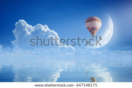 Idyllic heavenly picture - colorful hot air balloon, two seagulls flying in blue sky with white clouds and crescent above serene sea. Dream come true concept.Elements of this image furnished by NASA