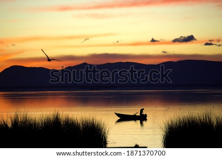 Idyllic image of a fisherman at sunrise on a still water lake with reeds in the foreground and a bird flying towards the mountains in the background Stockfoto ©