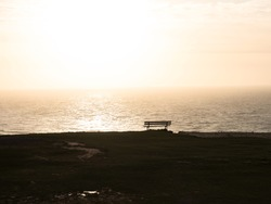Idyllic isolated bench bank seat on cliff overlooking atlantic ocean coast beach sea in Etretat Normandy France Europe