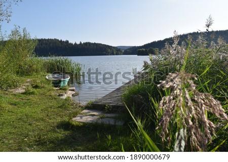 Photo of  Idyllic lakeside landscape, Boat, footbridge and island on Ratscher Lake, Talsperre Ratscher, Heckengereuth, Thuringia, Germany