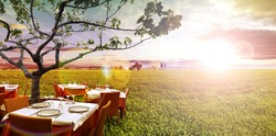 Idyllic outdoor restaurant in the green fields and sunset
