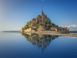 Idyllic panoramic view of famous Le Mont Saint-Michel tidal island with clear water and beautiful reflections on a sunny day with blue sky in summer, Normandy, northern France