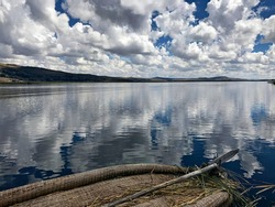 Idyllic peaceful summer day on Titicaca lake with mirror reflection of heaven clouds in calm water. Stunning waterscape from boat to magnificent Titicaca, Andes, Puno, Peru. Serenity and tranquility.