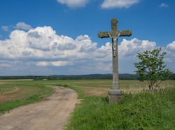 idyllic rural landscape with old stone cross with Jesus Christ statue, crucifix, dirty road, green fields, hills, tree and blue sky white fluffy clouds