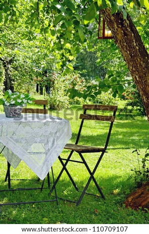 Idyllic setting of a small coffee table and a wooden chair under an apple tree in green summer garden