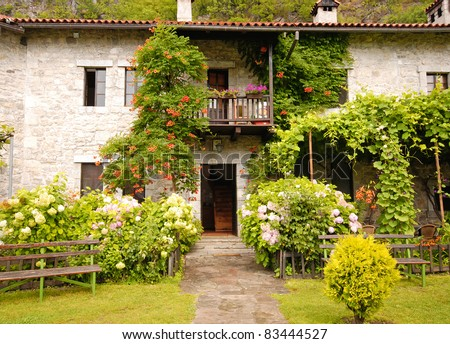 Idyllic stone cottage with pretty  garden. in european village - stock photo