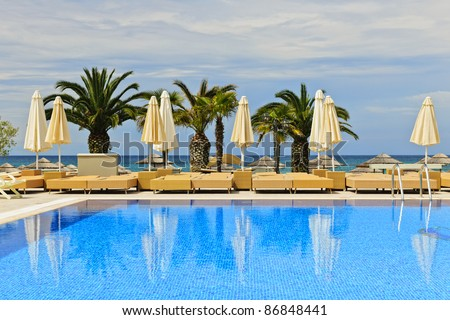 Idyllic swimming pool at tropical resort with palm trees in Greece