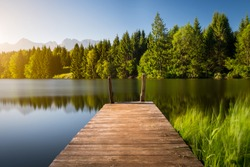 Idyllic view of the wooden pier in the lake with mountain scenery background. Alps in the early morning.