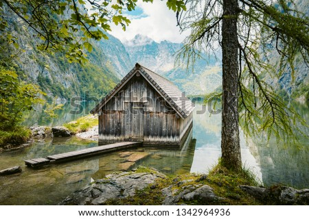 Idyllic view of traditional old wooden boat house at scenic Lake Obersee on a beautiful sunny day with blue sky and clouds in summer, Nationalpark Berchtesgadener Land, Bavaria, Germany #1342964936
