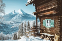 Idyllic view of traditional wooden mountain cabin in scenic white winter wonderland mountain scenery on beautiful cold sunny day with blue sky in the Alps