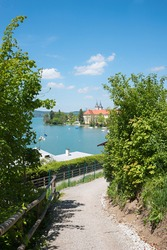 idyllic walkway with stunning view to lake tegernsee and castle, upper bavarian tourist resort