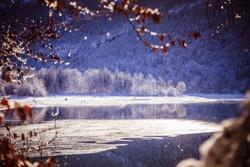 Idyllic winter landscape: Reflection lake, snowy trees and mountains