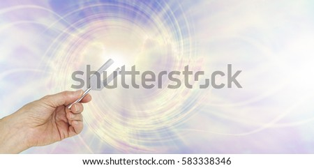 If you could see the sound waves make by an Angel Tuning Fork - female hand holding a short aluminum tuning fork on a graphic depiction of angelic sound waves background