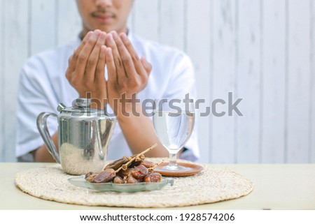 Iftar dish with muslim man hand praying to Allah. Dates fruit with glass of mineral water and teapot on the table. Traditional Ramadan, iftar meal. Ramadan kareem fasting month concept.