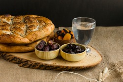 Iftar meal (time to break the fast) with sweet dry dates,apricot,black olives,water and Ramadan bread on the wooden board.Beginning meal before main menu.
