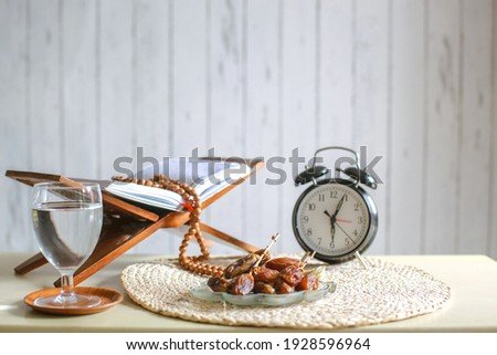 Iftar time cincpet. Kurma or dates fruit with glass of  water, holy Quran, alarm clock showing 6 o'clock and prayer beads on the table.