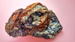 igneous andesite altered in hydrothermal alteration zone, with vein quartz, chlorite and shiny black pyrite minerals, on a pink background. Indonesia, geological exploration.
