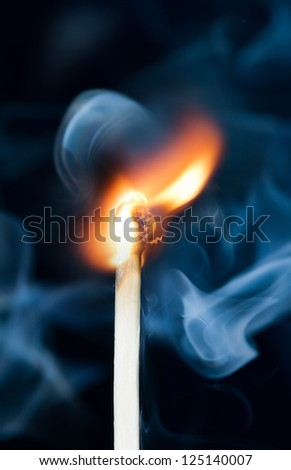 Ignition of match with smoke, isolated on black background