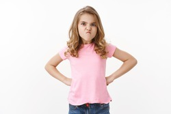 Ignorant moody childish cute little blond kid daughter showing character, sulking frowning displeased, grimacing hold hands waist angry offended, complaining whining want computer, white background
