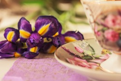 IIris flowers and traditional porcelain tea cup with saucer with floral paining . Spring, summer  background. Selective focus, side view