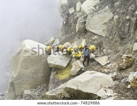 IJEN VOLCANO, INDONESIA - JAN 10: Worker carrying sulfur inside Ijen crater on January 10, 2011 in Ijen Volcano, Indonesia. He carries the load of around 90kg to the top of the rip and then 3 km down.