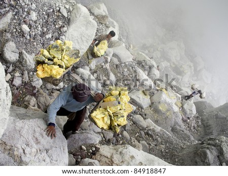 IJEN VOLCANO, INDONESIA - JAN 10: Worker carrying sulfur inside Ijen crater on January 10, 2011 in Ijen Volcano, Indonesia. He carries the load of around 60kg to the top of the rip and then 3km down.