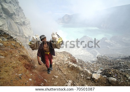 IJEN VOLCANO, INDONESIA - JUNE 29: Worker carrying sulfur inside Ijen crater on June  29, 2010 in East Java, Indonesia. He carries the load of around 90kg to the top of the rip and then 3 km down.