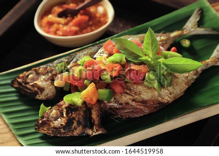 Ikan Tude Bakar Sambal Dabu. A popular dish of grilled Minahasan mackerel fish topped with Sambal Dabu, the Minahasan chopped chili salsa. Photo stock ©