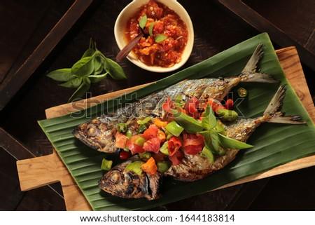 Ikan Tude Bakar Sambal Dabu. A popular Minahasan dish of grilled mackerel fish topped with Sambal Dabu-Dabu (Minahasan chopped chili salsa). Photo stock ©