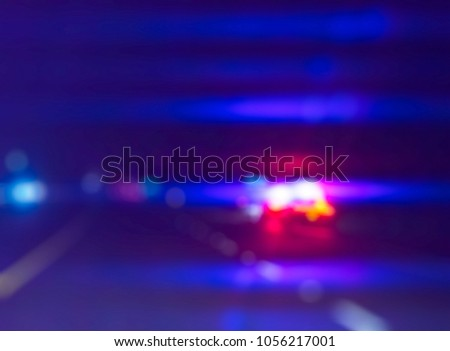 ilghting  of police car  on sideroad  at night while catching driver.  -blurred picture.