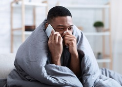 Ill Black Man Calling Doctor Having Runny Nose Suffering From Cold And Rhinitis Sitting On Sofa At Home. Sick African Guy Talking On Phone Feeling Unwell. Symptoms. Influenza Symptoms