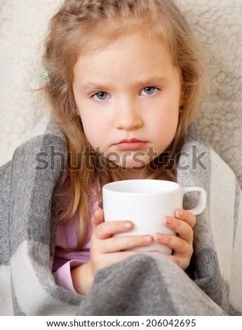 Ill child. Little girl wrapped in a blanket with mug