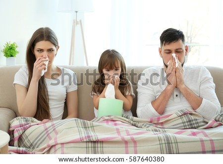 Ill family sitting on sofa at home