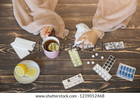 ill girl with a flu is sitting at the wooden table with pills and tea. Runny nose and cold. Weak immunity. Winter illness. Lemon and paper tissues. Treat and cure concept.