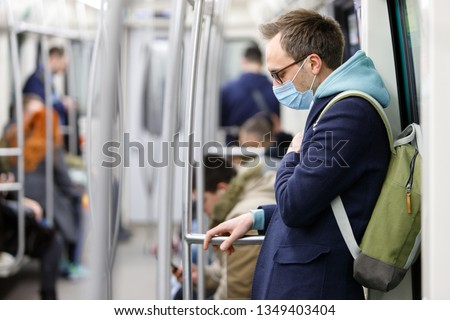 Ill man in eyeglasses feeling sick, wearing protective mask against transmissible infectious diseases and as protection against the influenza in public transport. New coronavirus 2019-nCoV from China
