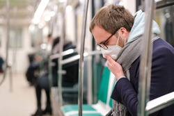 Ill man in glasses feeling sick, coughing, wearing respirator N95 mask against transmissible infectious diseases and as protection against the flu, coronavirus/covid-19 in public transportation