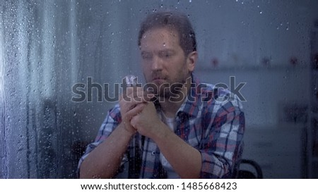 Ill man reading pills dosage form behind rainy window worrying about side effect