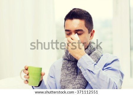 ill man with flu drinking tea and blowing nose #371112551