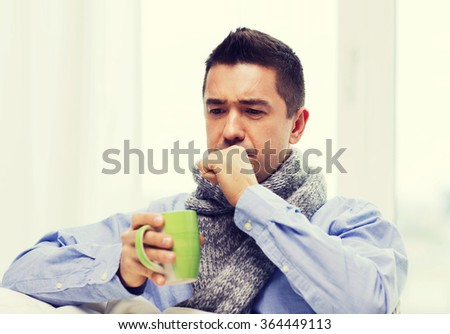 ill man with flu drinking tea and coughing at home #364449113
