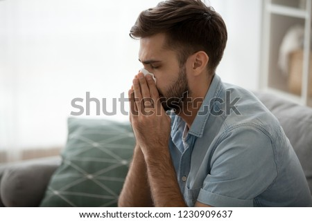 Ill millennial man sit on couch feel unwell blowing running nose with napkin, sick male at home have health problems, get flu or fever symptoms, tired guy suffer from sickness sneezing holding tissue Stock photo ©