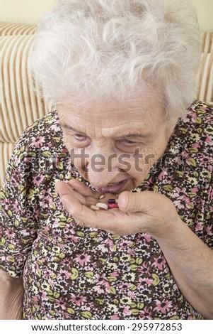 ill senior woman taking pills