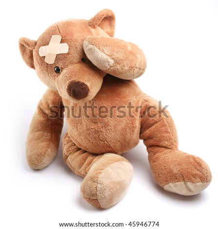 Ill teddy bear with plaster on its head. Isolated on a white background.