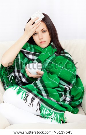 Ill woman covered with blanket, hold hand on forehead check temperature, holding cup of tea and pack of pills, sitting at home on sofa couch