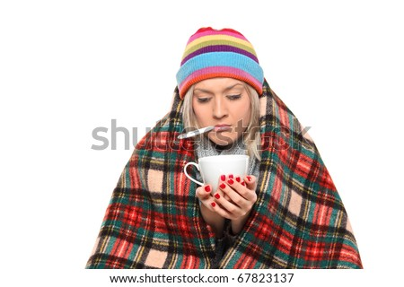 Ill woman covered with blanket holding a tea cup and a thermometer in her mouth isolated on white background